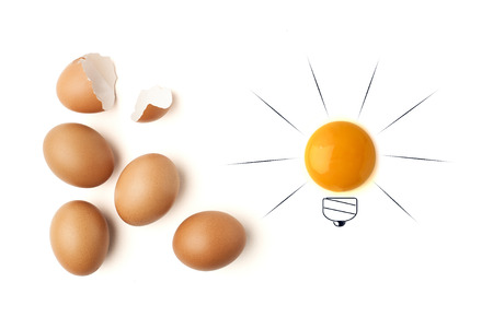 different thinking: Egg yolk ball forming a shape of illuminated light bulb on isolated white background Stock Photo