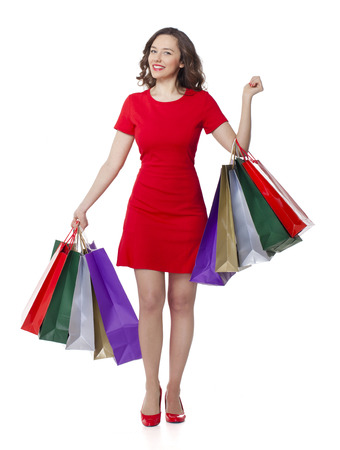 Full length portrait of beautiful young woman holding many colorful shopping bags isolated on white background