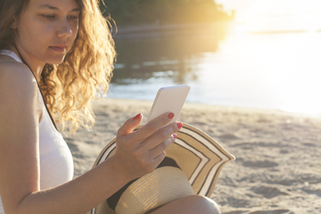 Woman with mobile phone on the beach