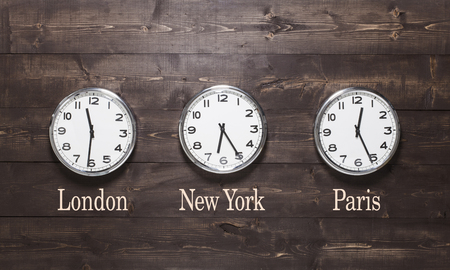Clocks on a wooden background with time zone of different country. London, New York, Paris.