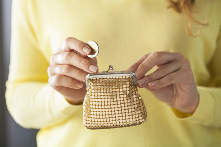 Young woman hands holding coin and small money pouch. Stock Photo