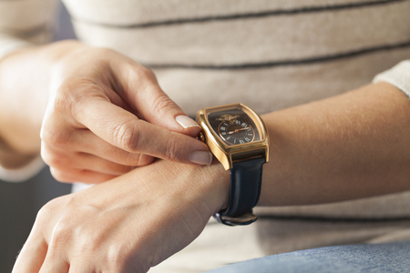 Close up of a woman winding her wrist watch Stock Photo