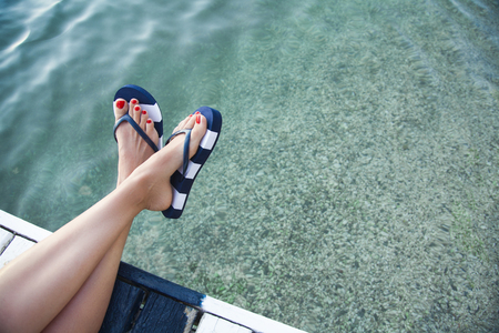 Woman feet with blue flip flops on the pier