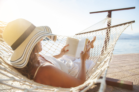 Woman in a hammock with book on summer day 免版税图像 - 124593714