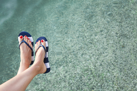 Woman feet with blue flip flops and sea
