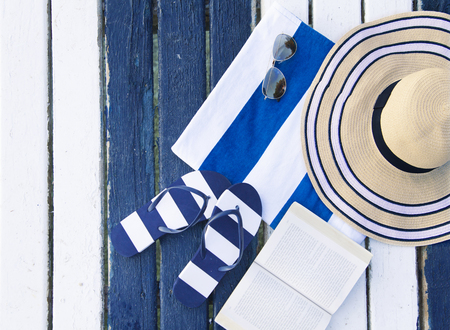 Striped blue flip flops, book and straw hat on the pier