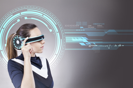 Young woman with futuristic smart glasses over gray background