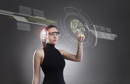 Attractive young woman touching the virtual future interface