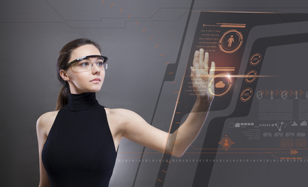 Young woman in a black high-tech dress is wearing smart glasses and pressing her hand up against a holographic screen Imagens - 124594061