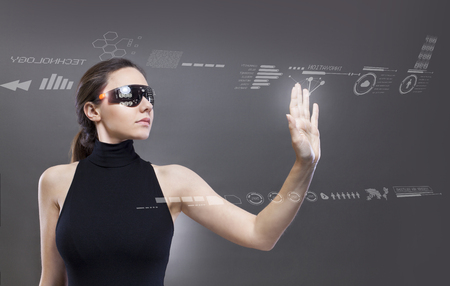 Young woman in a black high-tech dress is wearing smart glasses and pressing her hand up against a holographic screen Imagens - 124594070