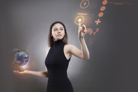 A young woman in a black high-tech dress and pressing her hand up against a holographic screen Imagens - 124594082