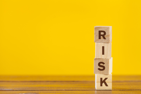 Risk word made with wooden blocks on yellow background. Risk management concept.