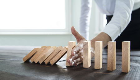 Businesswoman stopping falling wooden dominoes effect