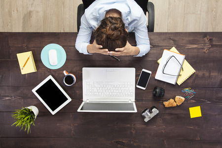 Stressed business woman sitting at office table and holding head in hands. Shot from above. Stock Photo