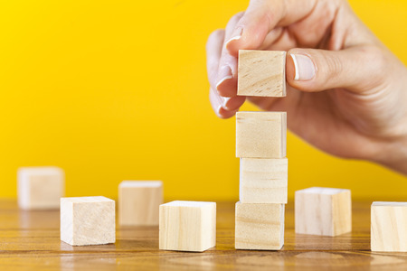 Woman hand arranging blank wooden cubes, business concept, mock up, template Banco de Imagens