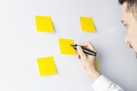 Businessman putting his ideas in sticky-note planning on business strategy