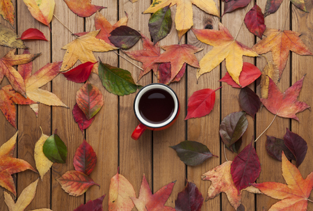 Autumn scene with cup of coffee and leaves on old wooden table