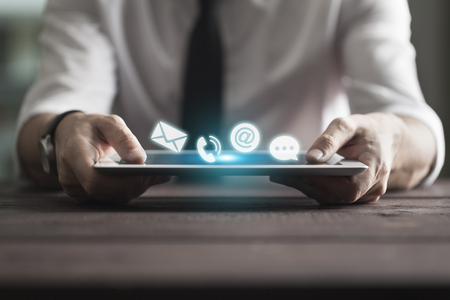 Businessman holding tablet pc. Communication concept, application icons flying around