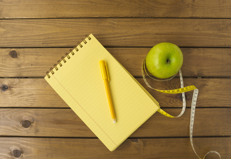 Empty notebook and apple on wooden table