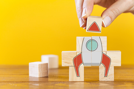 Hand arranging wooden cubes in a structure rocket shape. Conceptual of business startup and strategy. Фото со стока