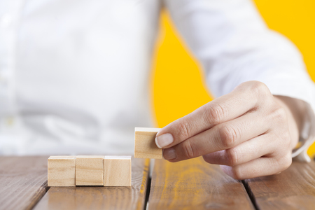 Woman hand arranging blank wooden cubes, business concept, mock up, template Фото со стока