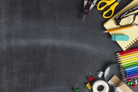 School supplies on black board background. Back to school concept Фото со стока