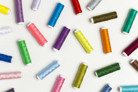 Multicolor sewing threads on white background