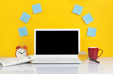 Laptop with blue blank sticky note and alarm clock on table on yellow background. mock up