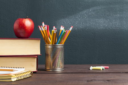 Back to school background with books and apple over blackboard Фото со стока
