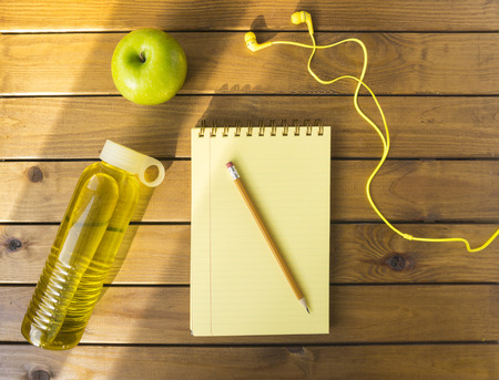 Pencil, Notebook and Apple on a Wood Background
