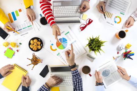 Geschäftsleute, die an einem Schreibtisch arbeiten und zwei Kollegen, die aufeinander zeigen Standard-Bild