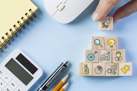 Startup concepts with business strategy symbols on wooden cubes. Flat lay. Фото со стока