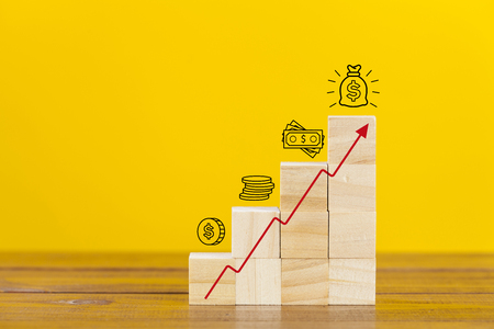 Rising earnings chart made from wooden cubes. Business growth success process. 写真素材