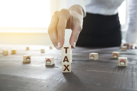 Businesswoman arranging wooden cubes with TAX word. Concept for mortgage and property owner