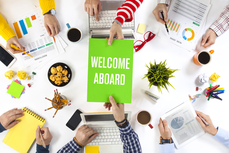 Young entrepreneur giving welcome on board written paper to new colleague Фото со стока