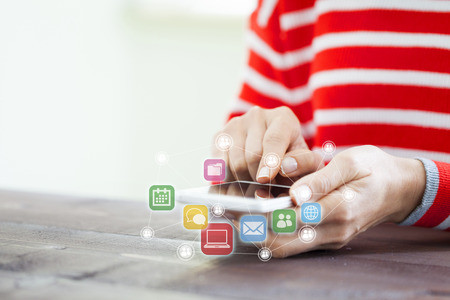 Woman hand using smart phone with application icons flying around