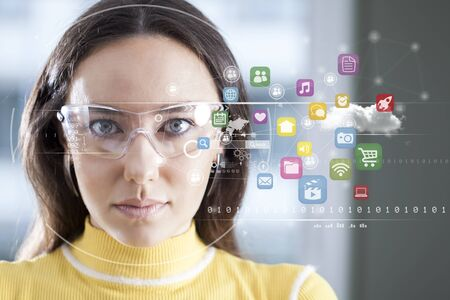 Young woman looking at virtual graphics in blurry background