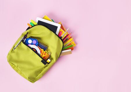 Backpack with school supplies spilling out pink ground. Back to School concept. Banco de Imagens