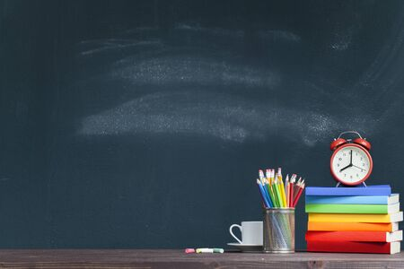 Red clock on rainbow colored books in classroom. Back to school concept Stok Fotoğraf - 128815031