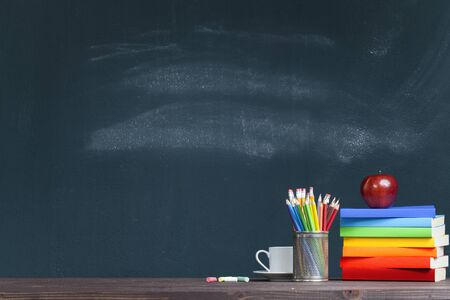 An apple on rainbow colored books in classroom. Back to school concept Stok Fotoğraf