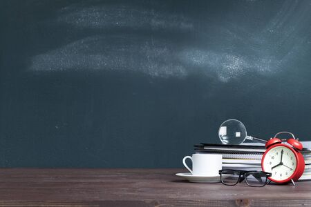 Magnifying glass on notebook stack in classroom. Back to school concept