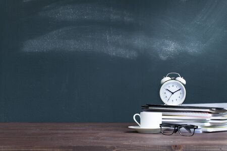White alarm clock on notebook stack in classroom. Back to school concept Banco de Imagens