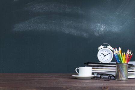 White alarm clock on notebook stack in classroom. Back to school concept Stok Fotoğraf - 128815480