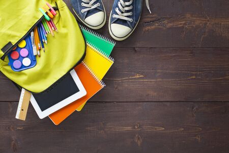 Back to school concept. Backpack with school supplies. Top view. Wooden background. Copy space. Stok Fotoğraf