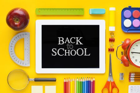 School stationery items on yellow background, text