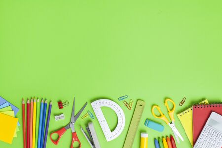 School stationery items on green background. Back to school concept. Stok Fotoğraf - 128815555