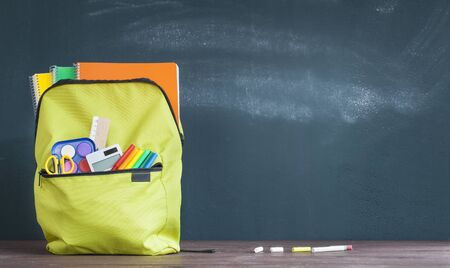 Backpack with school supplies front on the chalkboard Stok Fotoğraf - 128815586