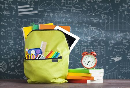 Student backpack with supplies in front of blackboard. Back to School concept Stok Fotoğraf