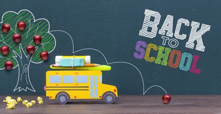 Back to school concept. Yellow school bus passing by the apple tree. Front view banner for your design.