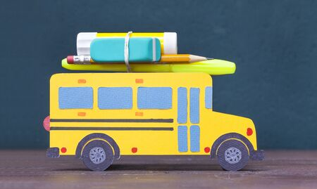 Back to school concept. Paper-cut model yellow school bus on the blackboard background Stok Fotoğraf - 128815734